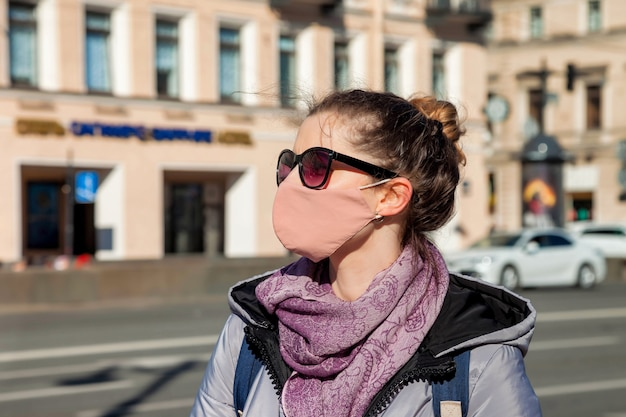 Covid-19-konzept. porträt einer sozialen touristin in der stadt, die eine medizinische maske gegen das krankheitsvirus sars-cov-2 trägt. frau mit gesichtsmaske, die während des pandemischen coronavirus 2019 unter einhaltung der distanz geht
