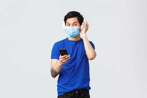 Covid-19-lebensstil, emotionen und freizeit der menschen im quarantäne-konzept. hübscher asiatischer hipster in medizinischer maske, mit kopfhörern musik hören, lied auf smartphone legen, handy halten