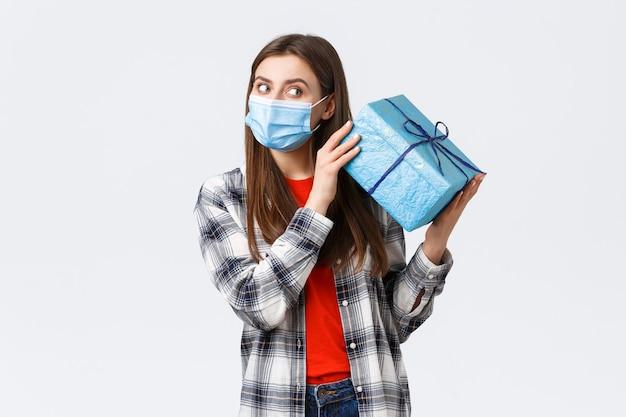 Covid-19, lifestyle, feiertage und feierkonzept. nettes geburtstagsmädchen in medizinischer maske, geschenkbox schütteln, um zu erraten, was drin ist, geburtstagsgeschenk erhalten und während der coronavirus-selbstquarantäne feiern