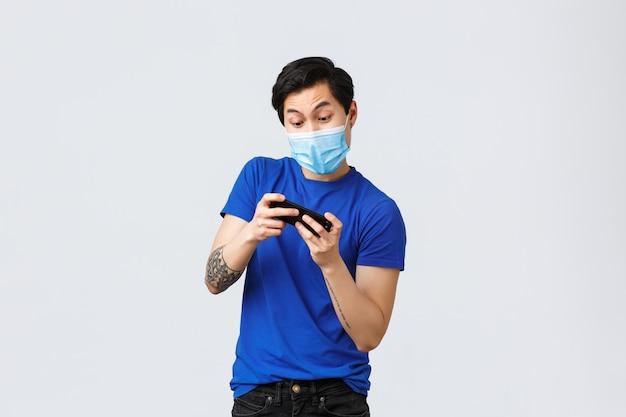 Covid-19-lifestyle-konzept. sorgloser junger asiatischer mann, der neues arcade- oder rennspiel auf smartphone spielt, kippt, während handy benutzt, medizinische maske tragen