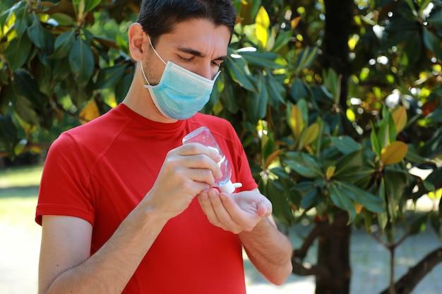 Covid-19 nahaufnahme des sportlichen mannes mit der chirurgischen maske unter verwendung der hände des alkohol-gel-desinfektionsmittels im stadtpark.