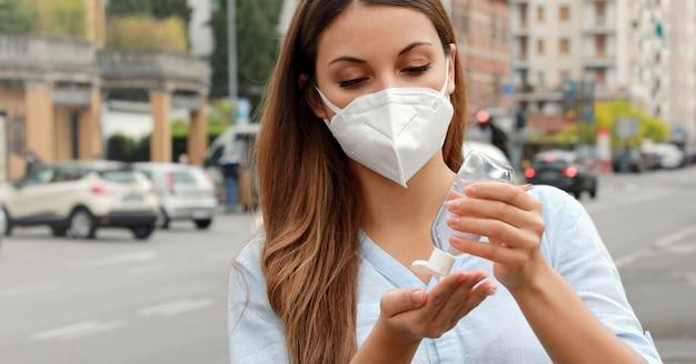 Covid-19 pandemic coronavirus close up frau mit ffp2-maske mit alkohol gel sanitizer hände in der city street.