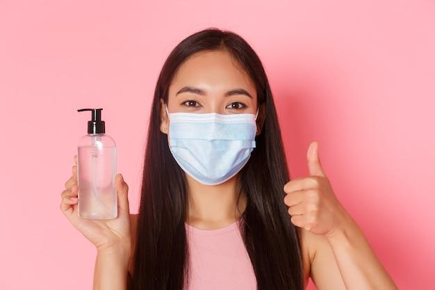 Covid-19-pandemie, coronavirus und soziales distanzierungskonzept. zufriedenes, fröhliches asiatisches hübsches mädchen in medizinischer maske, empfehlen antiseptikum, zeigen daumen hoch, während sie händedesinfektionsmittel zeigen, rosa wand
