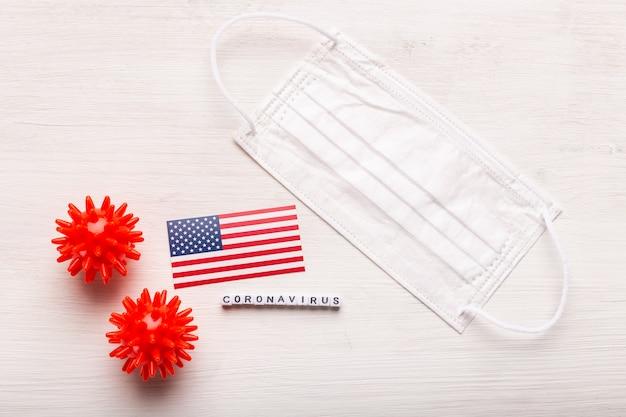 Covid-19, pandemie-, quarantäne- und viruskonzept - coronavirus-zellen mit amerikanischer usa-flagge und medizinischer schutzmaske auf weißem hintergrund.