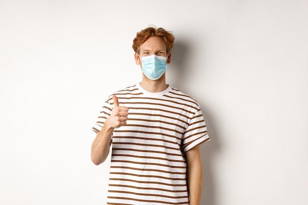 Covid-19, pandemie und konzept der sozialen distanzierung. junger mann mit roten haaren, der eine medizinische maske trägt, um das einfangen von coronavirus zu verhindern, daumen hoch, weißer hintergrund.