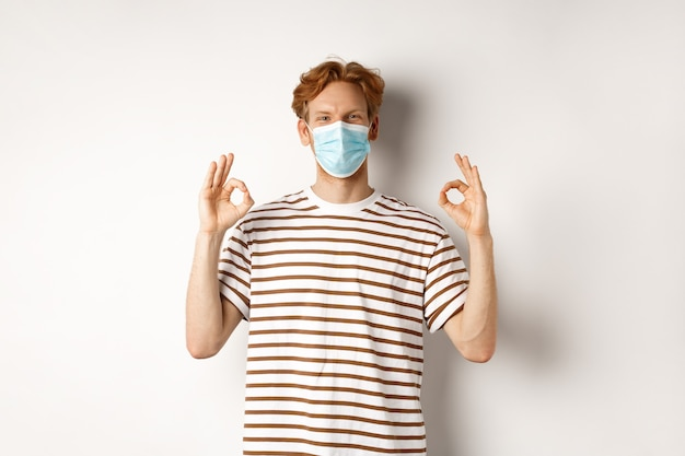 Covid-19, pandemie und konzept der sozialen distanzierung. junger mann mit roten haaren, der eine medizinische maske trägt, um das einfangen von coronavirus zu verhindern, mit guten zeichen zur genehmigung, weißer hintergrund