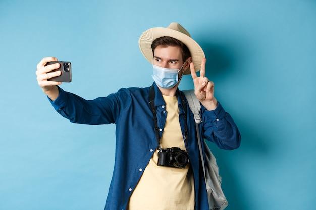 Covid-19, pandemie und reisekonzept. glücklicher und positiver kerl im touristenhut, der selfie nimmt und friedenszeichen zeigt, das nahe sightseeing, blauer hintergrund aufwirft.
