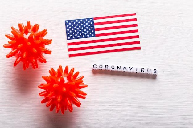 Covid-19, pandemie- und viruskonzept - coronaviruszellen mit amerikanischer usa-flagge auf weißem hintergrund.
