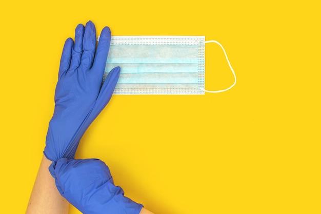 Covid-19-prävention flacher hintergrund, arzt in gummihandschuhen verwendet und hält eine medizinische gesichtsmaske auf einem hellgelben hintergrund