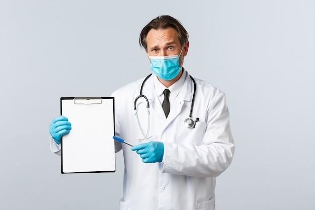 Covid-19, prävention von viren, gesundheitspersonal und impfkonzept. besorgter und verwirrter männlicher arzt in medizinischer maske und handschuhen, der auf die zwischenablage mit informationen oder diagnose zeigt