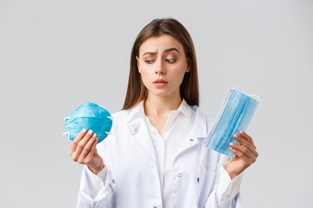 Covid-19, prävention von viren, konzept für gesundheitspersonal. neugieriger und unentschlossener arzt in peelings, atemschutzgerät betrachten, medizinische maske halten, nicht sicher, welche persönliche schutzausrüstung gewählt wird