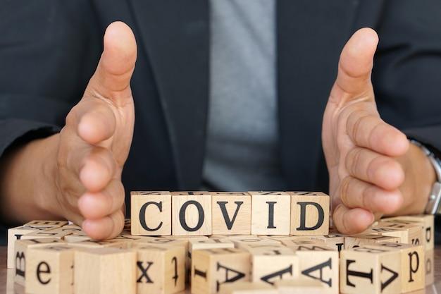 Covid-19 schreibt in holzbuchstaben ähnlich wie in einem scrabble-spiel