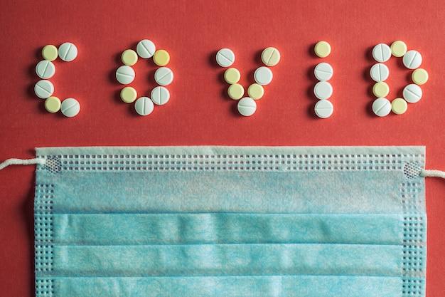 Covid 19 schriftzug aus weißen medizinischen pillen auf einer leuchtend roten oberfläche