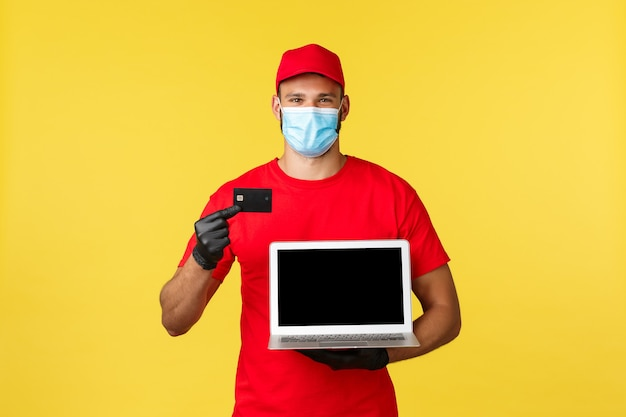 Covid-19, sicheres einkaufen, expressversand und auftragsverfolgungskonzept. lächelnder kurier in medizinischer maske, uniform, mit kreditkarte und webseite auf dem laptop-bildschirm, kontaktlose einfache zahlung