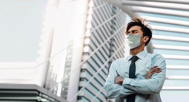 Covid-19-situation im geschäftskonzept. geschäftsmann mit der chirurgischen maske, die in der stadt steht