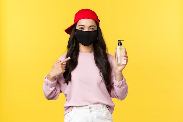 Covid-19, sozial distanzierender lebensstil, verhindert das konzept der virusverbreitung. lächelndes hübsches asiatisches mädchen in gesichtsmaske und roter kappe, die mit dem finger auf handdesinfektionsmittel zeigt, empfehlen hygieneprodukt.