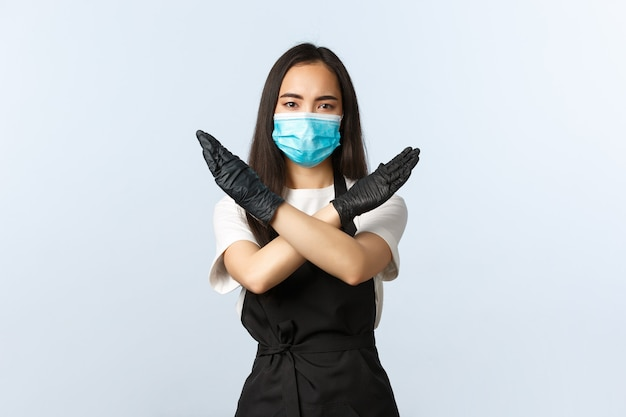 Covid-19, soziale distanzierung, kleines café-geschäft und präventionskonzept für viren. ernster junger barista, asiatisches café-personal verbietet kunden, ohne medizinische maske hineinzukommen, zeigt kreuzstoppschild