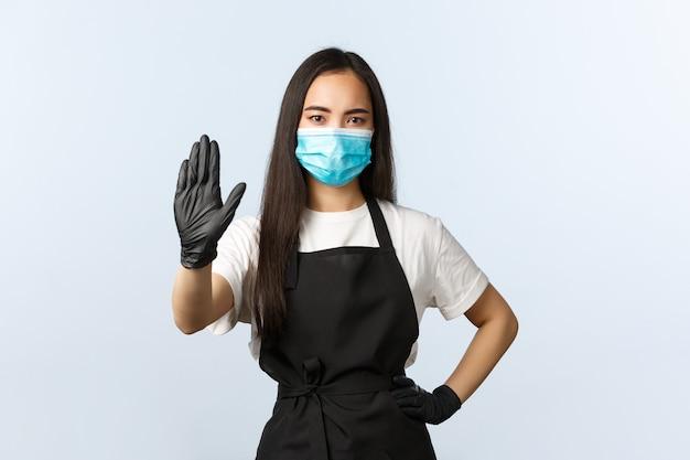 Covid-19, soziale distanzierung, kleines café-geschäft und präventionskonzept für viren. ernsthafte asiatische café-mitarbeiterin, barista zeigt stoppschild in medizinischer maske und handschuhen, verbietet das betreten des ladens