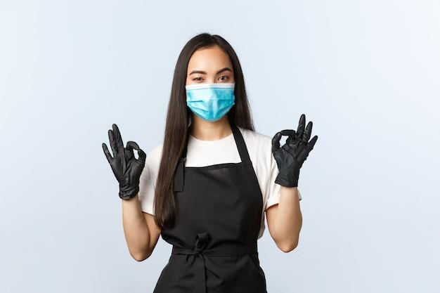 Covid-19, soziale distanzierung, kleines café-geschäft und präventionskonzept für viren. mitarbeiter haben alles unter kontrolle, garantieren qualität, zeigen ein okay-zeichen, tragen medizinische maske und handschuhe