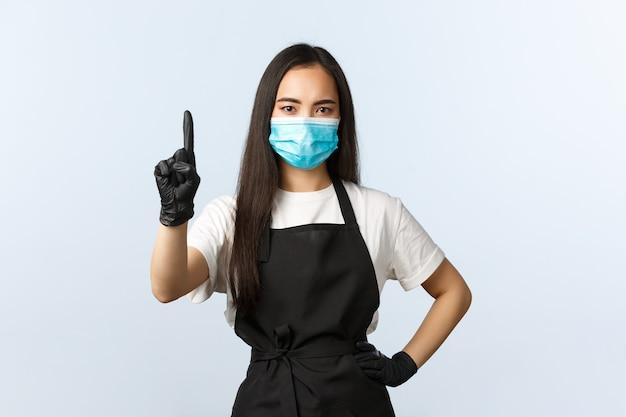 Covid-19, soziale distanzierung, kleines café und konzept zur verhinderung von viren. ernsthafte asiatische barista, cafébesitzerin erklärt die regel, schimpft oder verbietet, schütteln den finger, tragen eine medizinische maske und handschuhe