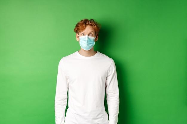 Covid-19, soziale distanzierung und lifestyle-konzept. junger rothaariger, der während der coronavirus-pandemie gesichtsmaske trägt und überrascht auf die kamera schaut, grüner hintergrund.