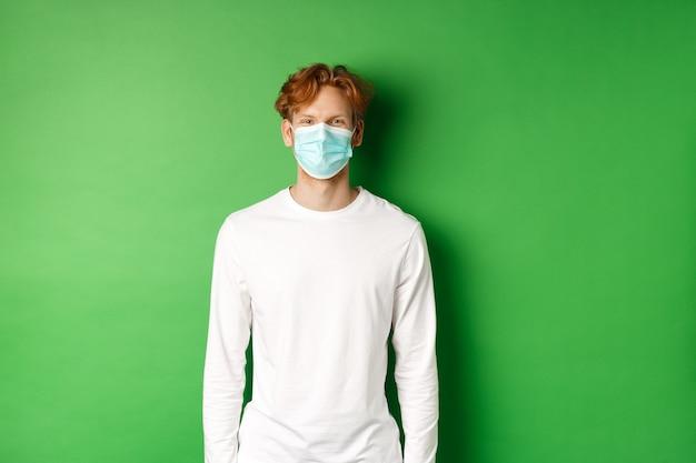Covid-19, soziale distanzierung und lifestyle-konzept. junger rothaariger mann, der während der coronavirus-pandemie gesichtsmaske trägt und auf grünem hintergrund steht.