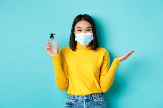 Covid-19, soziale distanzierung und pandemiekonzept. fröhliche asiatin, die händedesinfektionsmittel zeigt, empfiehlt die verwendung eines antiseptikums gegen coronavirus und trägt eine medizinische maske