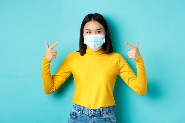 Covid-19, soziale distanzierung und pandemiekonzept. junge asiatische frau schützt sich vor coronavirus, zeigt mit dem finger auf ihre medizinische maske und steht auf blauem hintergrund