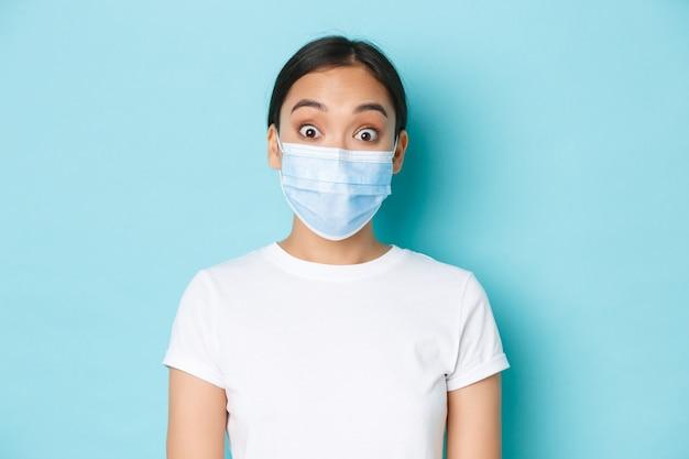 Covid-19, soziales distanzierungs- und coronavirus-pandemiekonzept. nahaufnahme des überraschten und erstaunten asiatischen mädchens in der medizinischen maske finden sie tolle neuigkeiten heraus, tragen sie eine medizinische maske, heben sie die augenbrauen hoch