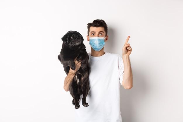 Covid-19, tier- und quarantänekonzept. junger mann in der medizinischen maske, die niedlichen schwarzen mops hält, hund, der rechts schaut und besitzer, der auf logo, weiß zeigt