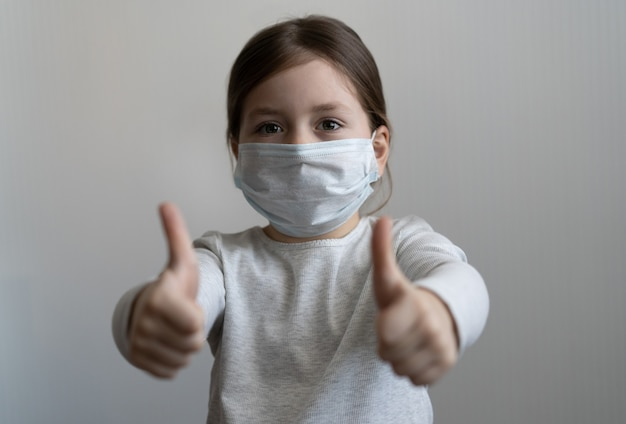Covid-19 und luftverschmutzungskonzept. kleines mädchen trägt maske zum schutz und daumen hoch geste für den ausbruch des koronavirus. coronavirus- und epidemische virussymptome