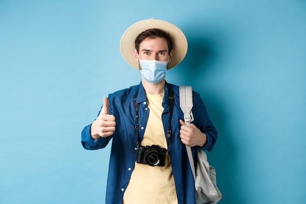 Covid-19 und sommerferienkonzept. lächelnder kerl, der in der medizinischen maske und im strohhut reist, rucksack und daumen hoch zeigt, reisebüro genehmigt und lobt, blauer hintergrund.