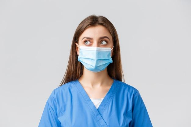 Covid-19, verhinderung von viren, gesundheit, beschäftigten im gesundheitswesen und quarantäne. nachdenkliche attraktive ärztin oder krankenschwester in medizinischer maske und peeling, sehen in der oberen linken ecke verträumt oder fasziniert aus