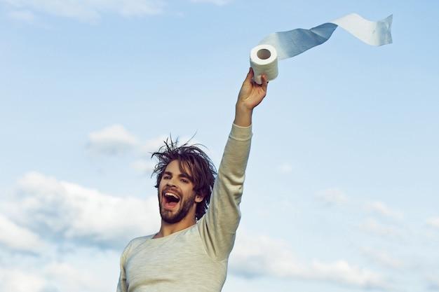 Covid, coronavirus. wc und toilette. sterilität und reinheit. mann mit glücklichem gesicht halten toilettenpapier auf blauem himmel. hygiene und hygiene. pandemie.