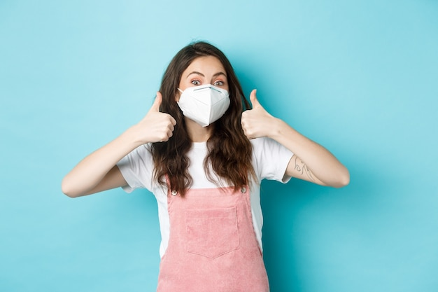 Covid-, gesundheits- und pandemiekonzept. fröhliche junge frau in atemschutzmaske zeigt daumen hoch zur zustimmung, empfiehlt etwas, steht vor blauem hintergrund.