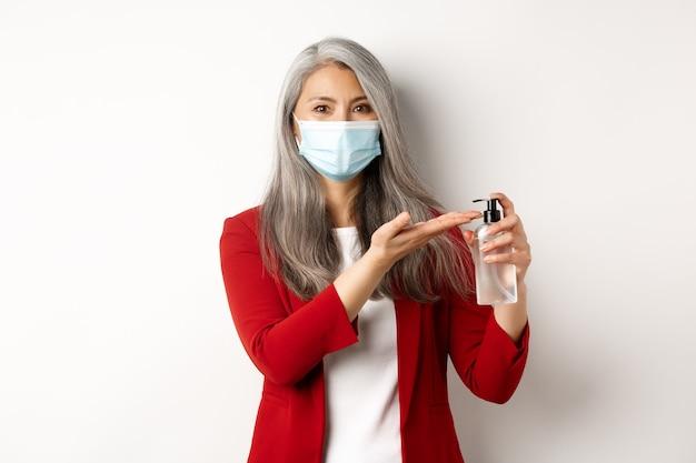 Covid, pandemie und geschäftskonzept. asiatische managerin in medizinischer maske mit händedesinfektionsmittel und lächelnd in die kamera, stehend mit antiseptikum auf weißem hintergrund