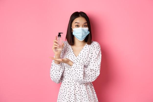 Covid-pandemie und lifestyle-konzept schöne koreanische frau in kleid und medizinischer maske, die handse...