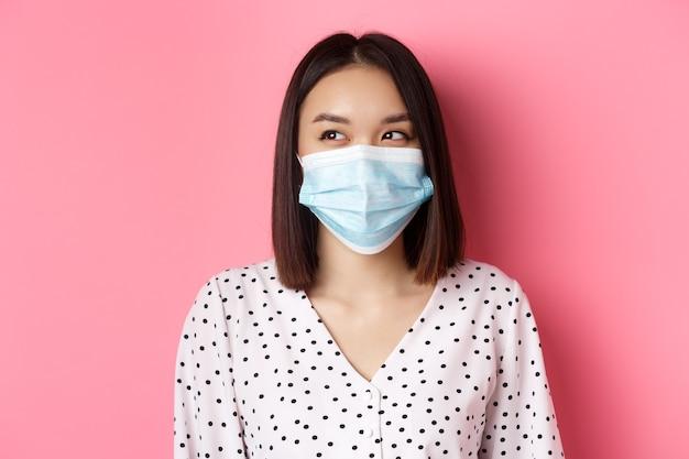 Covid-pandemie und lifestyle-konzept schönes asiatisches weibliches modell in medizinischer maske lachend lächelnd a...