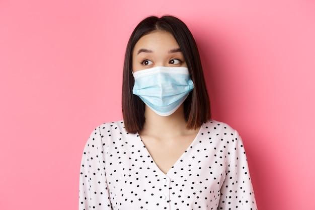 Covid-pandemie und lifestyle-konzept schönes asiatisches weibliches modell in medizinischer maske mit blick nach links auf co...