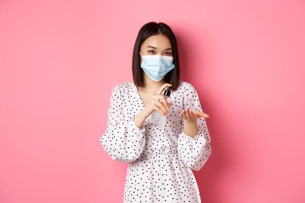 Covid-pandemie und lifestyle-konzept süße asiatische frau saubere hände mit desinfektionsmittel mit antiseptikum und...