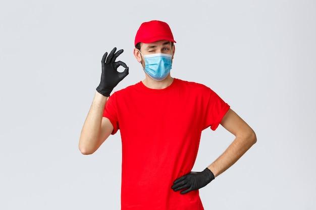 Covid-selbstquarantäne-online-shopping- und versandkonzeptlieferant in roter t-shirt-kappe mit gesichtsm...