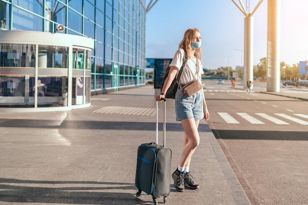 Covid travel airport woman tourist mit rucksack und koffer in der nähe des internationalen flughafens te...