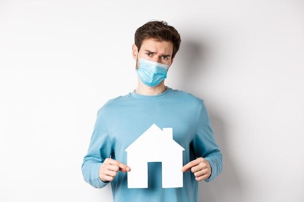 Covid und immobilienkonzept. trauriger und zweifelhafter junger mann in der medizinischen maske, die sich widerstrebend zeigt und papierausschnitt zeigt, der über weißem hintergrund steht.