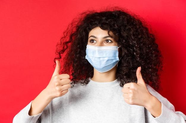 Covid- und pandemie-konzept, nahaufnahme einer jungen kaukasischen frau mit lockigem haar, die eine medizinische maske trägt...