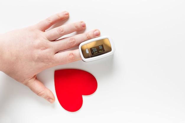 Covid valentinstag-konzept, hand mit pulsoximeter auf einem finger und einem herzsymbol auf weißem hintergrund