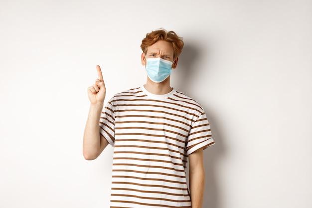 Covid, virus und soziales distanzierungskonzept. enttäuschter junger mann mit roten haaren, gesichtsmaske tragend, finger nach oben zeigend und missbilligend stirnrunzelnd, sich über promo beschwerend.