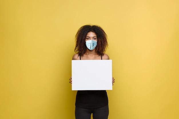 Covid19 concept - nahaufnahme porträt junger schöner attraktiver afroamerikaner mit gesichtsmaske, die einfaches weißes leeres zeichen zeigt.