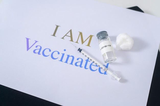 Covid19-coronavirus-impfstoffflaschen und spritzeninjektionswerkzeuge für die covid-19-immunisierung mit texthintergrund, ich bin geimpft.