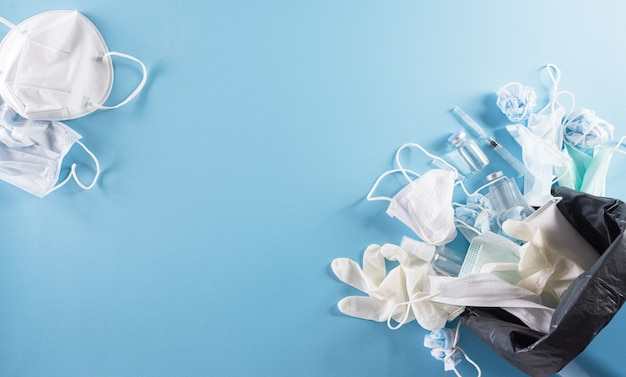 Covid19 einwegmasken für plastikmüll und müll, medizinische handschuh-alkohol-gel-flasche und nadel im mülleimer