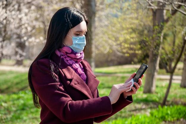 Covid19. junge frau in schützender steriler medizinischer gesichtsmaske im freien desinfiziert telefon antibakterielle serviette. coronavirus-konzept.